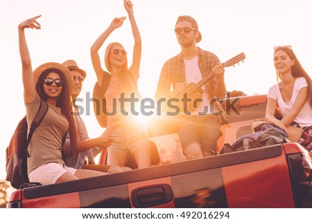 Road trip fun. Group of young cheerful people enjoying their road trip while sitting in pick-up truck together  #492016294