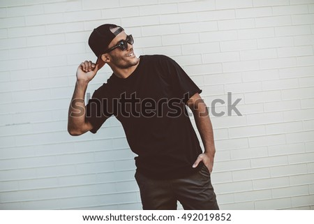 Always in good mood. Handsome young African man in black T-Shirt smiling and looking away while standing in front of the brick wall outdoors  #492019852