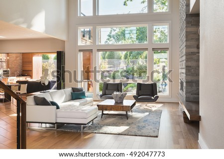 Beautiful living room interior in new luxury home with view of outdoor covered patio. Home interior with hardwood floors and open floor plan with vaulted ceilings #492047773
