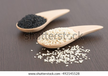 White sesame and black sesame seed in wooden spoon on wood table. #492145528