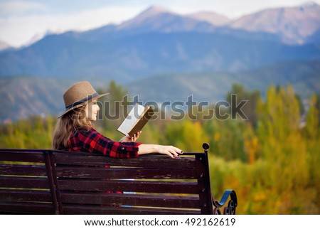 Woman in red checked shirt and hat sitting on the wooden bench and reading book at autumn forest and mountains background #492162619