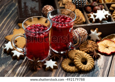 Christmas hot cranberry tea and cookies on dark background, closeup, horizontal #492179788