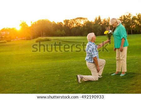 Man with bouquet is kneeling. Couple of seniors on meadow. This is for you, darling. Ho to impress a woman. #492190933