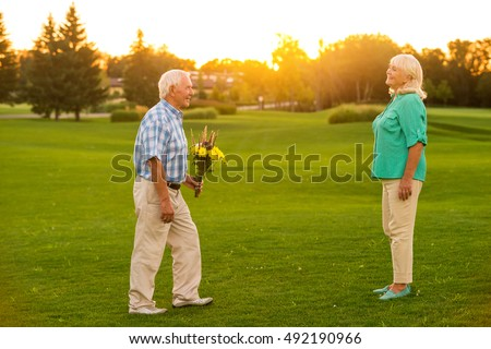 Senior man with a bouquet. Couple on a meadow. Let me congratulate you. Fifty years together. #492190966