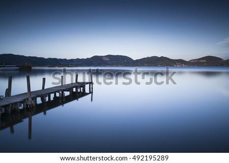 Wooden pier or jetty on blue lake sunset and sky reflection water. Long exposure, Versilia Massaciuccoli, Tuscany, Italy. #492195289
