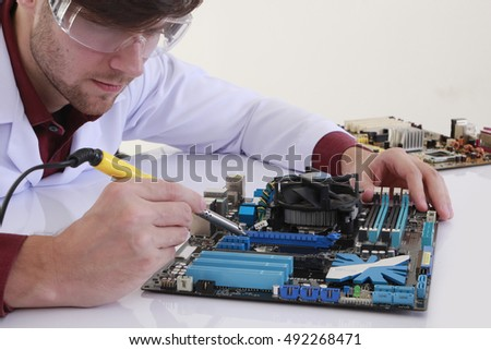 Male tech tests electronic equipment in service center #492268471