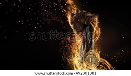Sport. Man's hand holding up trophy medal. Winner in a competition. Fire and energy Royalty-Free Stock Photo #492301381