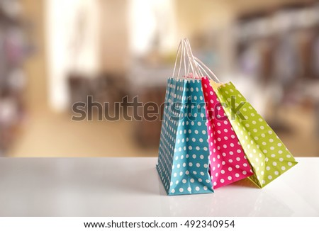 Three paper bags to buy colored with white circles in a row on white table in a shop. Front view #492340954