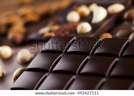 Dark and milk chocolate bar on a wooden table #492427111