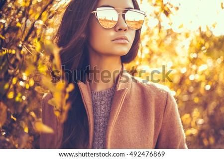Outdoor fashion photo of young beautiful lady surrounded autumn leaves #492476869