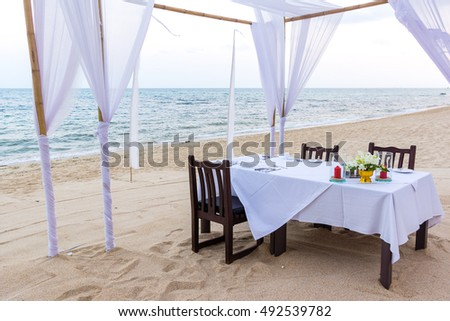 Romantic dinner table for three at a white beach  #492539782