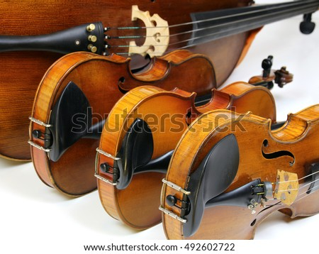 Instruments of a string quartet in a row: two violins, viola and violoncello Royalty-Free Stock Photo #492602722