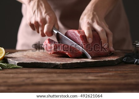 Butcher cutting pork meat on kitchen Royalty-Free Stock Photo #492621064