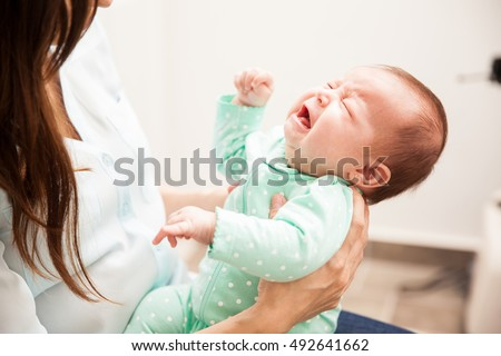 Portrait of a cute newborn baby crying in front of her mother while she holds her and tries to comfort her #492641662