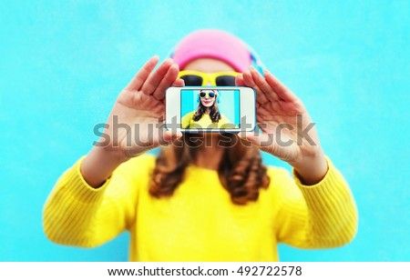 Fashion cool girl taking photo self portrait on smartphone over white background wearing a colorful clothes and sunglasses