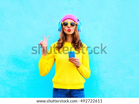 Fashion pretty sweet carefree woman listening music in headphones with smartphone wearing a colorful pink hat yellow sweater sunglasses over blue background #492722611