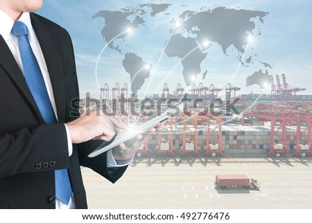 Import, Export, Logistics concept - Businessman press digital tablet to show global network partnership connection use for logistic,export background.(Elements of this image furnished by NASA)    #492776476