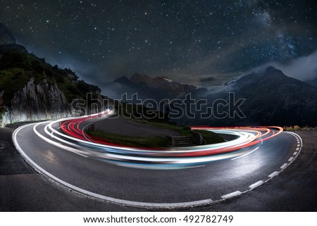light trails on a hairpin bend and milky way in the background. swiss alps pass road at night, starry sky with galaxy and car light trails #492782749