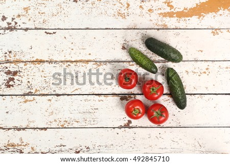 Tomatoes and cucumbers on peeled paint plank background. Directly Above. #492845710