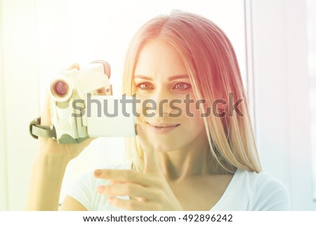 woman holds a home video camera in a light house #492896242