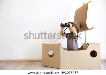 Little boy playing with cardboard ship on white wall background Royalty-Free Stock Photo #493035037