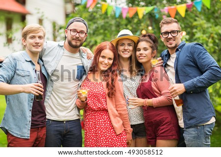 leisure, holidays, people, reunion and celebration concept - happy friends with drinks at summer garden party #493058512