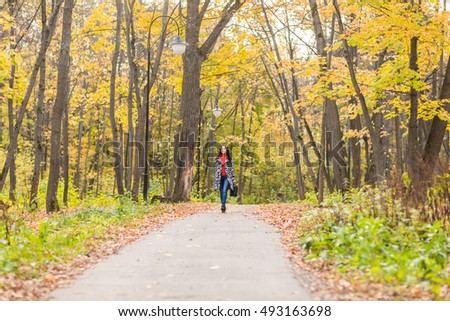 Autumn concept - Beautiful young modern woman walking in nature #493163698