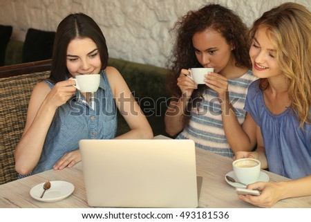 Happy friends with laptop drinking coffee in cafe #493181536
