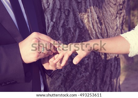 Hand of the groom and the bride wearing a wedding ring on the finger of his bride. #493253611