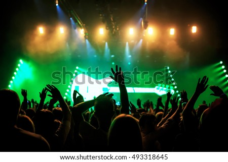 silhouettes of rock concert crowd in front of bright stage lights, green guitar on stage #493318645