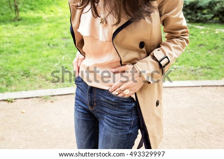 Fashion woman in a pink silk shirt and beige raincoat with trendy rings on her fingers. Beautiful brunette girl in jeans and autumn coat. #493329997