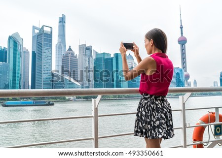 Asian business woman taking phone picture of Pudong skyline while on Shanghai ferry cruise towards the financial district center, China. Female tourist looking at view taking snapshots.