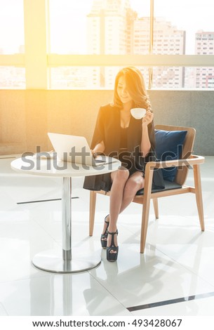 Business women sitting on wood chair while is sitting in skyscraper building,She thinking about work ,  laptop put on the modern table,She wear black suit and hold a cup of coffee #493428067