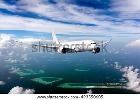 White passenger wide-body Dreamliner plane in flight. Aircraft is flying in blue cloudy sky over the sea and Maldivian islands and atolls. #493550605