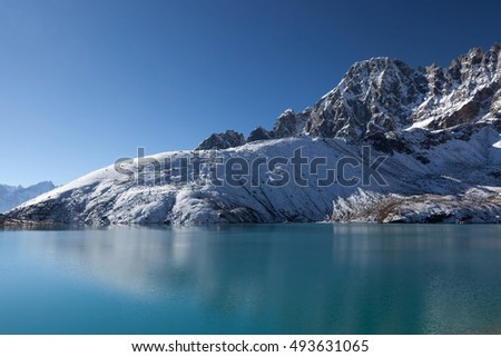 Beautiful Himalayan mountain range reflecting in ripples of Gokyo Lake's emerald green waters under the clear blue sky on a bright sunny day. Amazing mountain lake scenery. #493631065