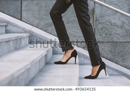 Legs and feet detail of businesswoman climbing stairs outdoors in Milan. Royalty-Free Stock Photo #493654135
