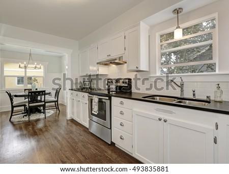 White kitchen storage combination and built in stainless steel appliances in kitchen room interior. Northwest, USA #493835881