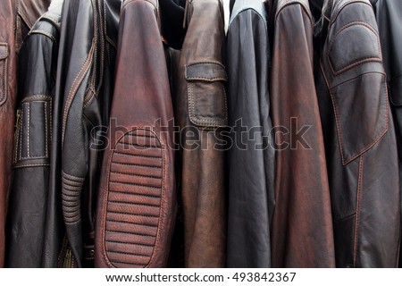 Collection of leather jackets on hangers in the shop. Many new men's leather winter jackets. Background and closeup texture of biker's leather, motorcycle jackets. Royalty-Free Stock Photo #493842367