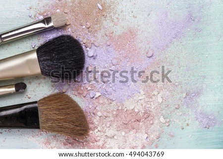 Makeup brushes on a teal blue background, with traces of powder and blush on it. A horizontal template for a makeup artist's business card or flyer design, with plenty of copyspace