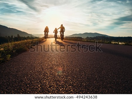 Bicycle family traveling on the road at sunset