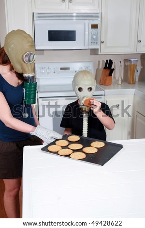 a mother and son enjoy peanut butter cookies in their kitchen while wearing gas masks in a post nuclear winter future #49428622