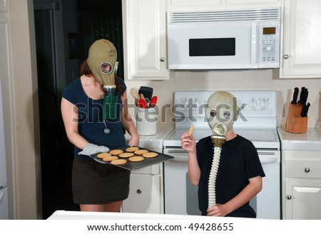 a mother and son enjoy peanut butter cookies in their kitchen while wearing gas masks in a post nuclear winter future #49428655