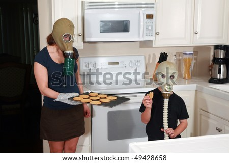 a mother and son enjoy peanut butter cookies in their kitchen while wearing gas masks in a post nuclear winter future #49428658