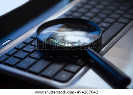 Selective focus on keyboard with magnifier searching concept in dark low key night tone