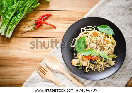 spicy sausage spaghetti topping with sweet basil prepare with red chili pepper and lettuce on black dish and wooden forks #494346709