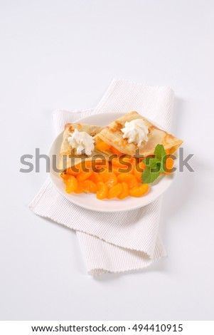 plate of pancakes with canned tangerines on white place mat #494410915
