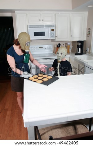 a mother and son enjoy hot fresh baked cookies in their kitchen while wearing gas masks in a post nuclear future #49462405