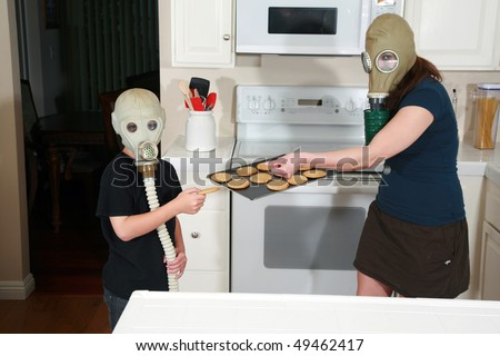 a mother and son enjoy hot fresh baked cookies in their kitchen while wearing gas masks in a post nuclear future #49462417
