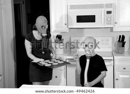 a mother and son enjoy hot fresh baked cookies in their kitchen while wearing gas masks in a post nuclear future in black and white for a edgy futuristic image #49462426