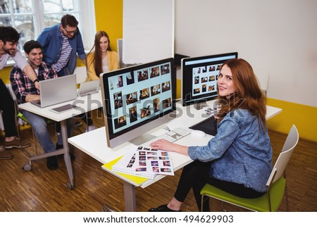 Attractive photo editor working on computers in the office